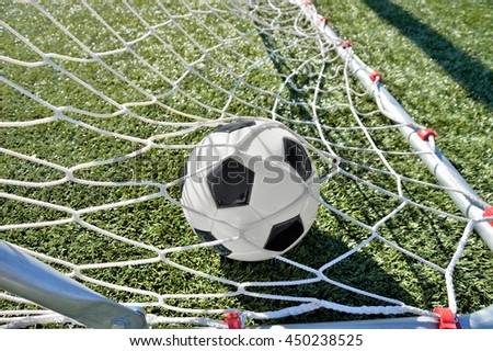close up of goal with a soccer ball in net   - stock photo