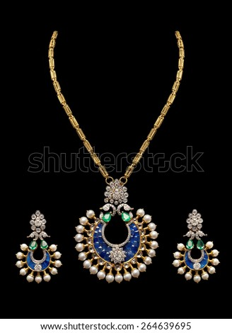 Close up of gold, diamond and pearl necklace on black background with earrings - stock photo
