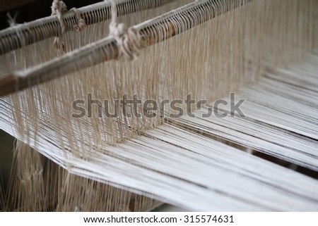Close up of gold silk weaving on loom, cotton on the manual wood loom in Asian traditional culture and woman lifestyle,Weaving shuttle on the warp. fashion fabric factory and business in Thailand.hand