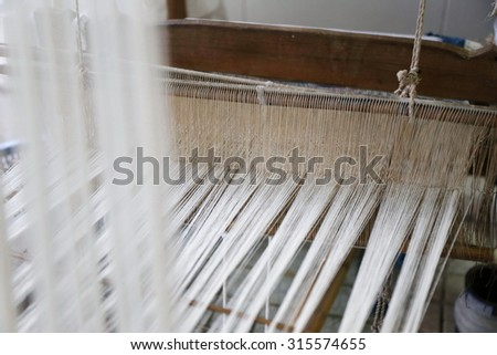 Close up of gold silk weaving on loom, cotton on the manual wood loom in Asian traditional culture and woman lifestyle,Weaving shuttle on the warp. fashion fabric factory and business in Thailand.hand - stock photo