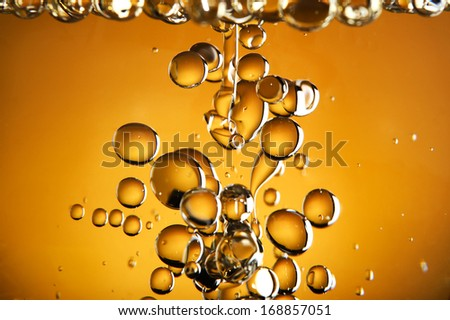 Close up of golden bubbles on illuminated background