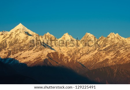 close up of golden colored snow clad himalayan peaks - stock photo