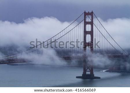 Close up of Golden Gate Bridge in San Francisco California on foggy morning surrounded with low lying clouds