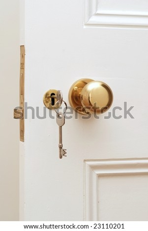 Close up of golden key at white door - stock photo