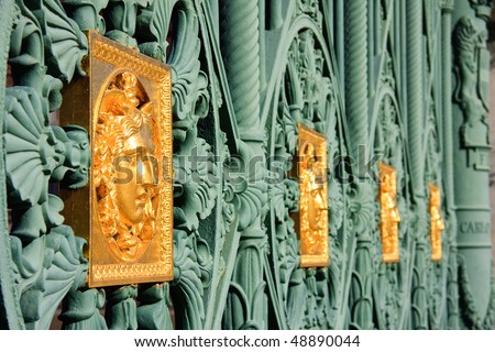 close up of golden masks with the fence in front of the royal palace in Turin - stock photo