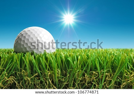 close up of golf ball in grass with sun in background - stock photo