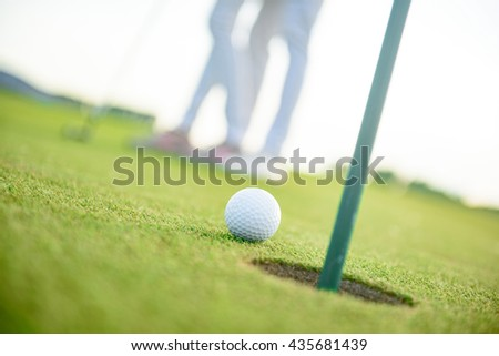 Close up of golf ball next to hole