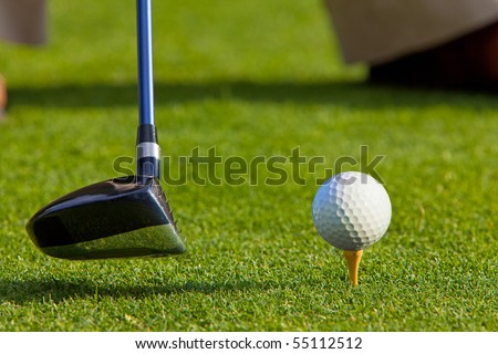 Close up of golf ball on a tee with the driver positioned ready to hit the ball. The golfer's feet and shoes are partially visible in the background.