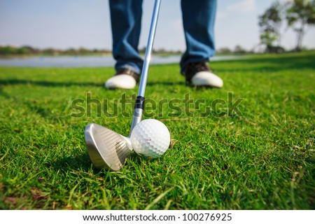 Close up of golf ball on green grass with the driver positioned ready to hit the ball - stock photo