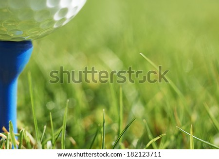 Close-up of golf ball resting on blue tee with grass and space for copy - stock photo