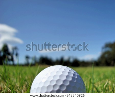 close up of golf ball with fairway and trees blurred off into distance - stock photo