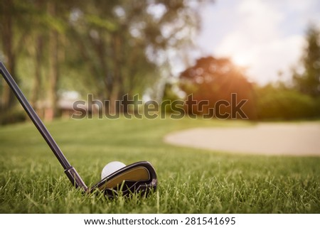 Close up of golf club with ball on tee, with fairway in background at sunset. - stock photo