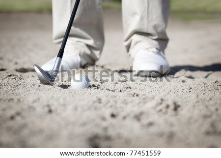 Close up of golf player pitching ball in bunker. - stock photo