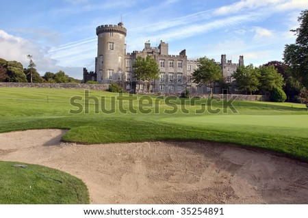 close up of golf sand bunker by golf green and castle - stock photo