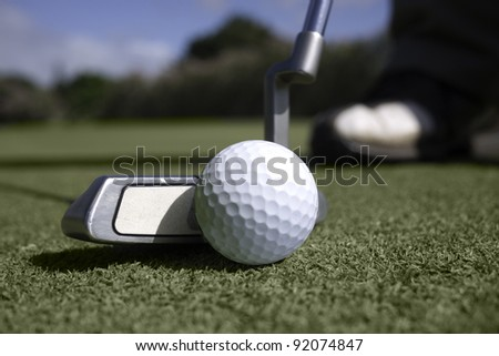 Close up of golfer's putter addressing the golf ball on the putting green.