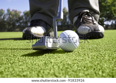 Close up of golfer setting up for a putt on the putting green. - stock photo