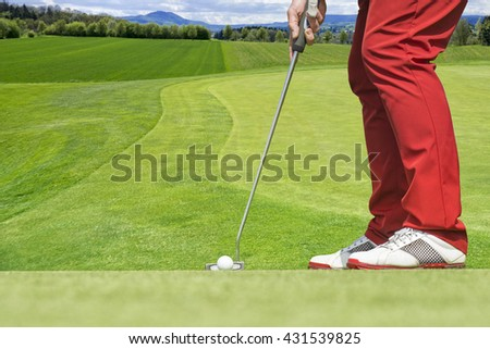 Close up of golfer with red trousers who concentrates to hit the ball.