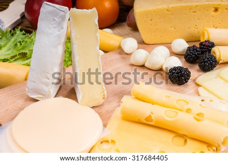 Close Up of Gourmet Cheese Board Appetizer Featuring Brie, Swiss and Provolone Cheeses Garnished with Berries - stock photo