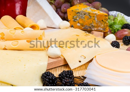 Close Up of Gourmet Cheese Board Featuring Variety of Cheeses and Garnished with Fresh Fruit - Tasty and Plentiful Cheese Board Appetizer - stock photo