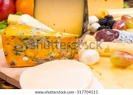 Close Up of Gourmet Cheese Board Featuring Variety of Cheeses, Cured Meat and Garnished with Fruit - Detail of Appetizing Cheese Board - stock photo