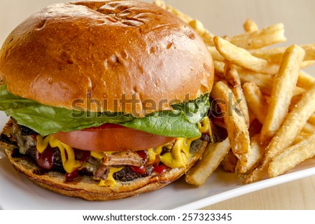 Close up of gourmet pub hamburger with bacon on white plate with side of french fries sitting on wooden table - stock photo