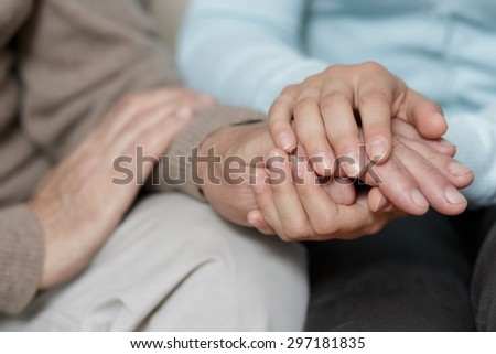 Close-up of granddaughter supporting her senior grandpa - stock photo