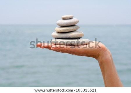 Close-up of gravel pile in woman's hands with sea background - stock photo