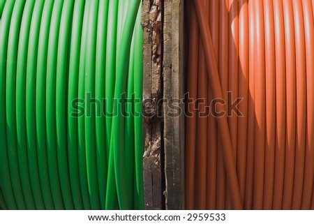 Close-up of green and red electricity cable on wooden spools. Green left, red right. - stock photo
