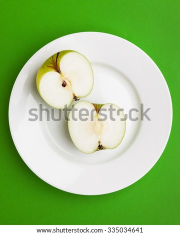 Close-up of green apple slice on white plate. - stock photo