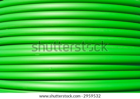 Close-up of green electricity cable horizontal on a spool.