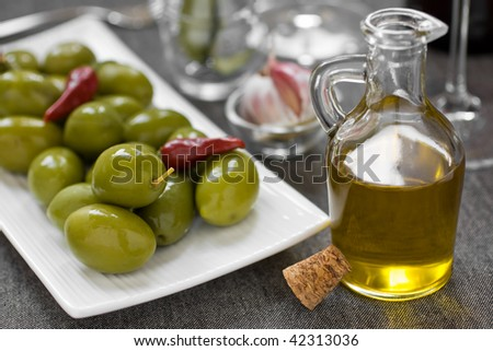 Close up of green olives and olive oil - stock photo