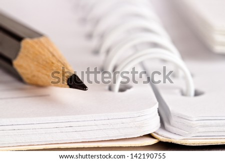 Close-up of grey pencil lying on spiral notebook