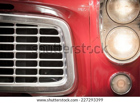 Close Up of Grille and Illuminated Headlights of Classic Red Vehicle - stock photo