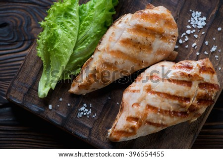 Close-up of grilled chicken breast filets with green salad - stock photo