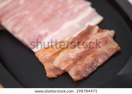 Close up of grilled or barbecued bacon or pork belly on black metal plate for food background - stock photo