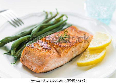 Close up of grilled salmon fillet with green beans and lemon on white plate - stock photo
