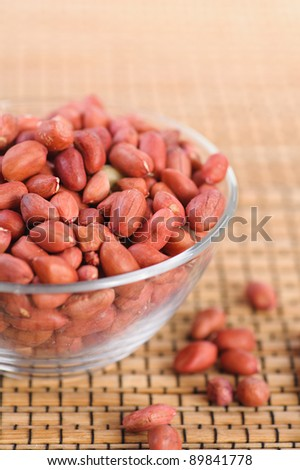 close-up of groundnut (peanut) in glass vase and few scattered on table - stock photo