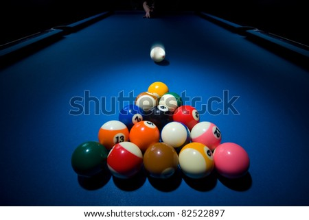 Close up of group of billiard ball is triangle shape and white ball coming fast towards them - stock photo