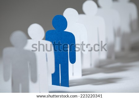 Close up of group of paper men standing in a row. Lots of similar copies of a paper man, but a blue one stands out among them - stock photo