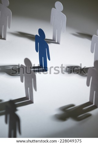 Close up of group of standing papermen. Lots of similar copies of a paper man, but a blue one stands out among them. Concept of teamwork and leadership - stock photo
