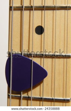 Close up of Guitar Pick on a Fret Board - stock photo