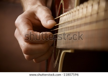 Close up of guitarist hand playing acoustic guitar - stock photo