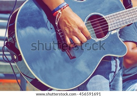 Close-up Of  Guitarist Male Hand And Fingers Who Touches String On The Black Acoustic Six String Guitar. Street Musical Band Play Latin Music - stock photo