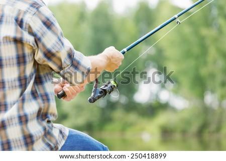 Close up of guy sitting on bridge and fishing - stock photo