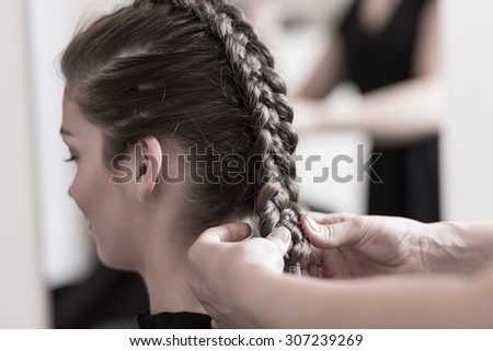 Close-up of hairdresser doing beautiful wedding hairstyle - stock photo