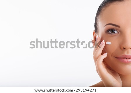 Close up of half of head of cheerful woman covering her cheek with cream. She is smiling gently. Isolated on white background and there is copy space in left side - stock photo