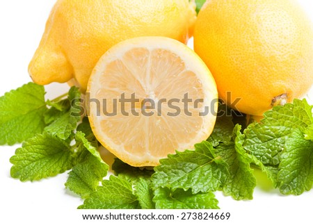 close up of halved lemon, with green lemon balm leaf and two citrus fruits on white background,  - stock photo