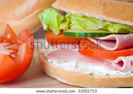 Close up of ham and cream cheese bagel with salad - stock photo