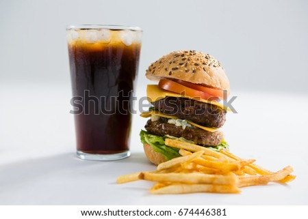 Close up of hamburger and drink with French fries against white background