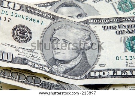 Close up of Hamilton on a ten dollar bill surounded by other bills